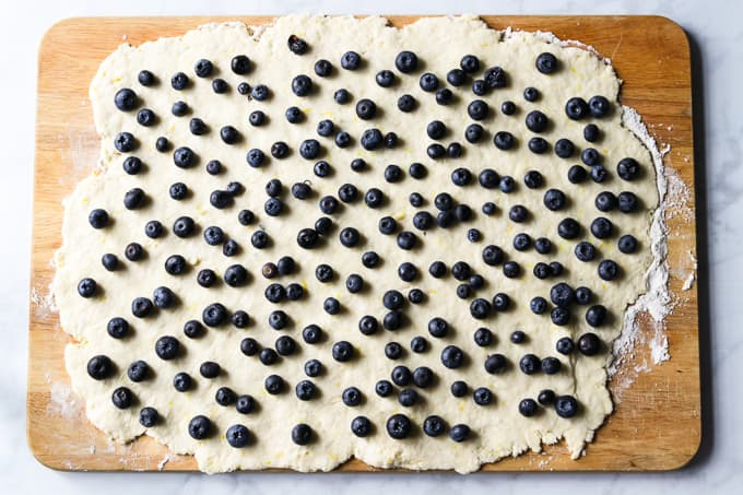 Rolled out pastry dough and topped with blueberries.