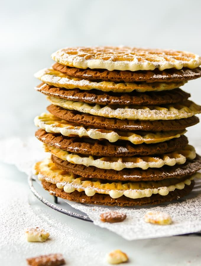 Anise and chocolate pizzelle cookies stacked up on a black wire rack.