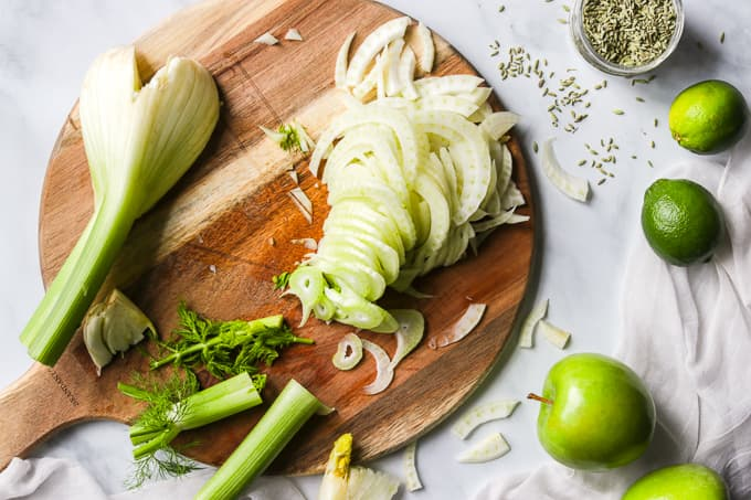 Thin slices of fennel on a cutting board.