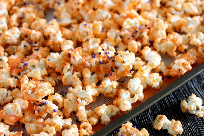 Orange chocolate popcorn on a baking sheet.