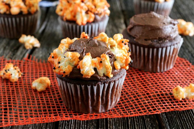 Decorating cupcakes with orange chocolate popcorn.