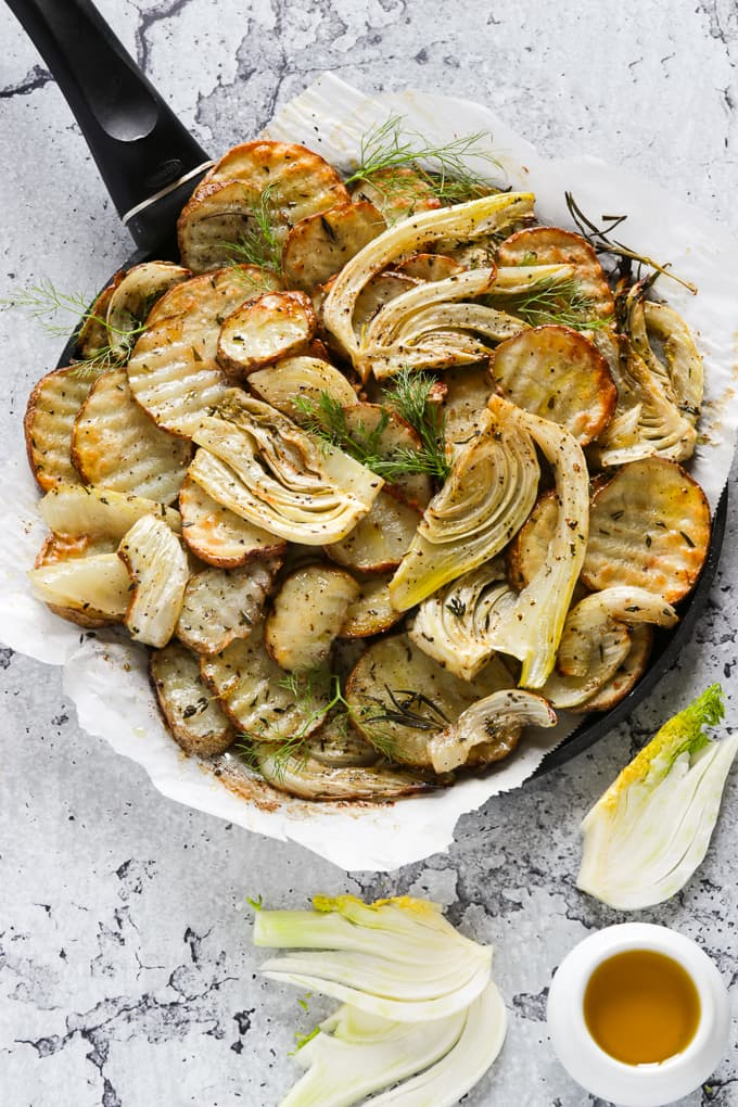 Oven roasted vegetables on a black pan.