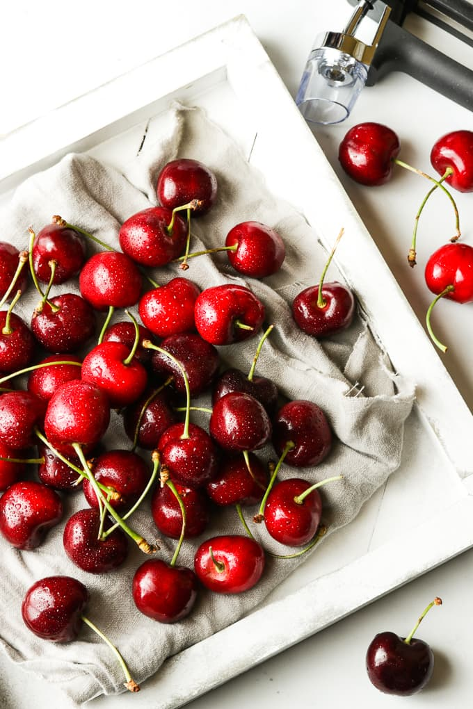Fresh cherries on a white wooden board.