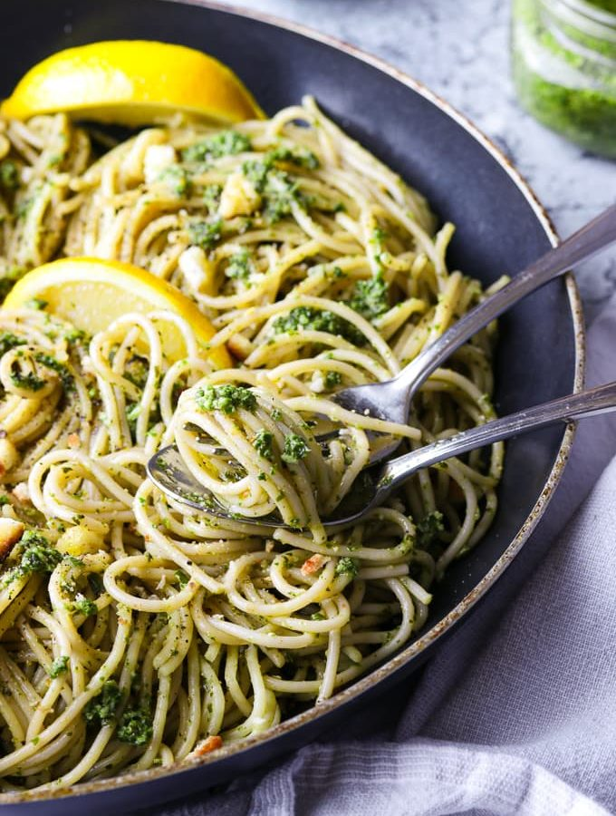 Spaghetti with walnut kale pesto in a skillet.